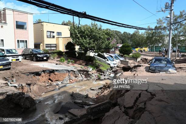 TOPSHOT A car is stuck on a road damaged by an earthquake in Sapporo Hokkaido prefecture on September 6 2018 A powerful 66magnitude quake rocked the...
