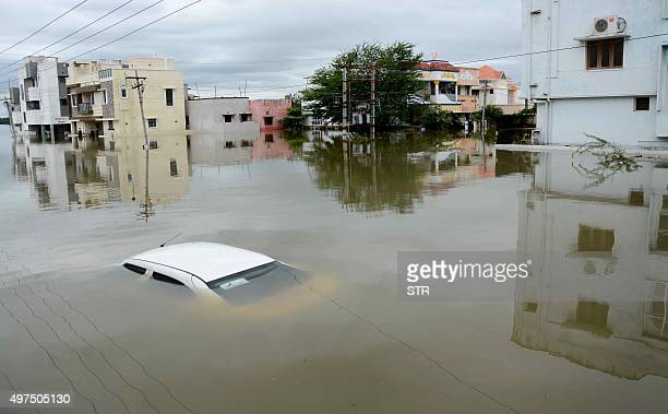 A car is submerged amidst waterlogged houses in a rainhit area of Chennai on November 17 2015 India has deployed the army and air force to rescue...