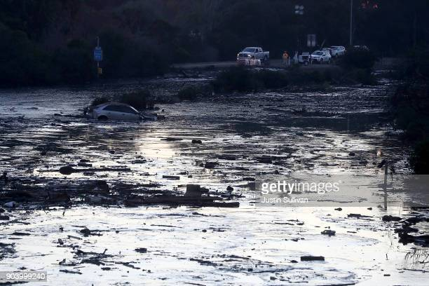 A car is submerged in muddy water in a flooded section of Highway 101 car on January 11 2018 in Montecito California 17 people have died and hundreds...