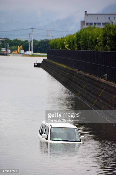 A car is sunken in a flooded road as torrential rain hits Kumamoto on July 1 22015 in Kumamoto Japan