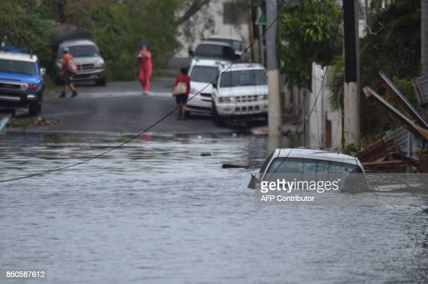 A car is viewed stuck in a flooded street in Santurce in San Juan Puerto Rico on September 21 2017 Puerto Rico braced for potentially calamitous...