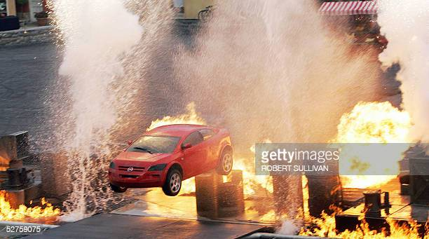 A car jumps through fire 04 May 2005 during a showing of Lights Motors Action Extreme Stunt Show at DisneyMGM Studios in Lake Buena Vista FL The show...
