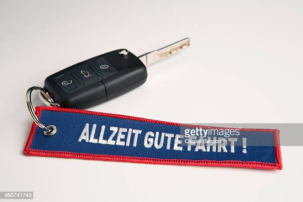 A car key and keychain with the phrase Always Drive Good in German Allzeit Gute Fahrt!