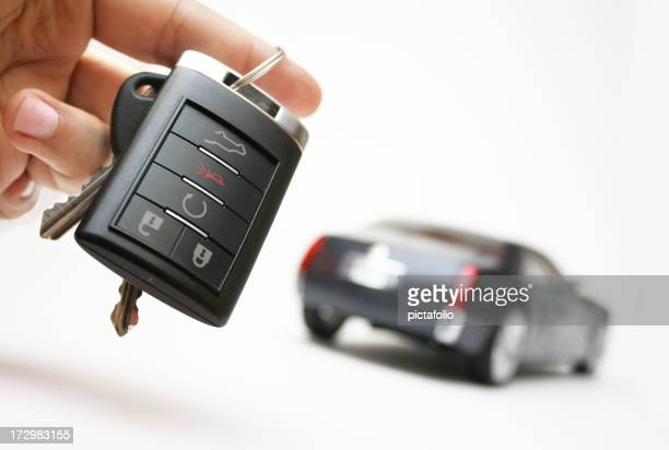Car keys in a hand with an unfocused car in the background
