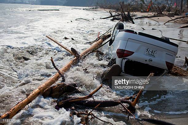 A car leans on a gate at the post office after the recent tsunami in Kesennuma city Miyagi prefecture on April 14 2011 Japan's seismologists were so...