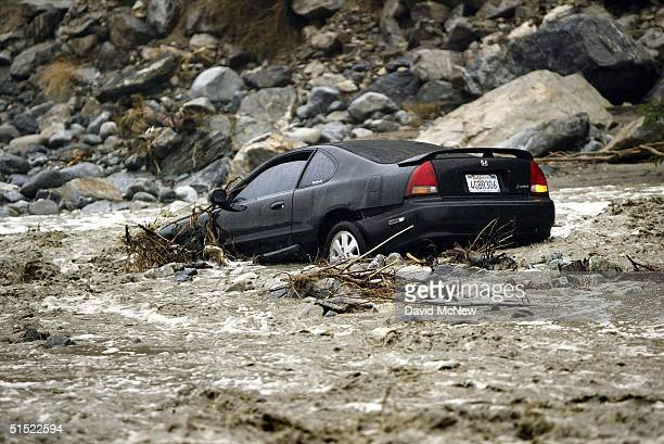 A car lies where it was swept away when its driver tried to cross the swollen waters of Lytle Creek on Lytle Creek Road the only way out for the...