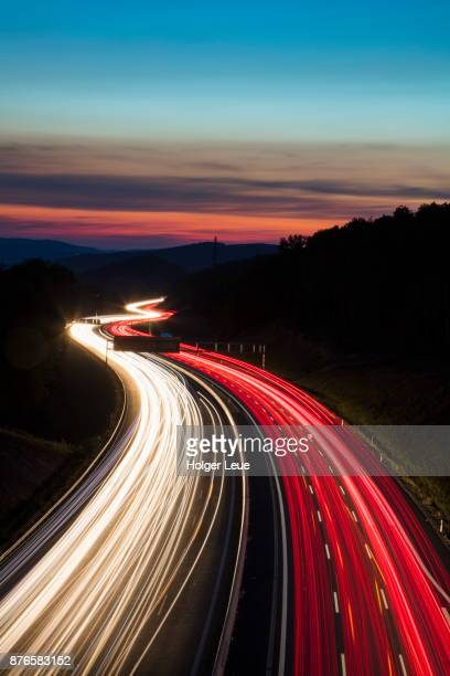Car light streaks on Autobahn A3 motorway connecting Würzburg and Frankfurt at dusk, Weibersbrunn, Spessart-Mainland, Franconia, Bavaria, Germany