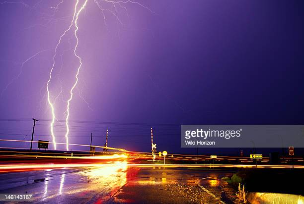 Car light trails and lightning with wet pavement and power lines near city street railroad crossing Tucson Arizona USA