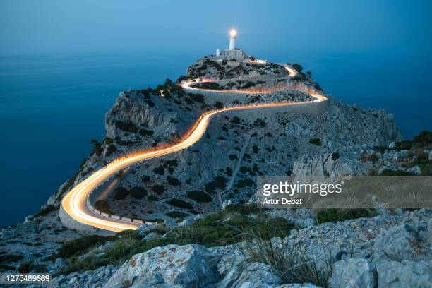 car light trails in curvy road with lighthouse and extreme terrain in the north of mallorca island. - light natural phenomenon ストックフォトと画像