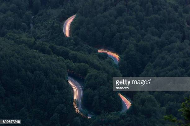 car light trails on winding mountain pass road kesselberg strasse, seen from mt. jochberg, bavaria, germany. - vehicle light stock photos and pictures