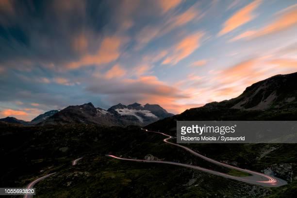 car lights, bernina pass, switzerland - hairpin curve stock photos and pictures