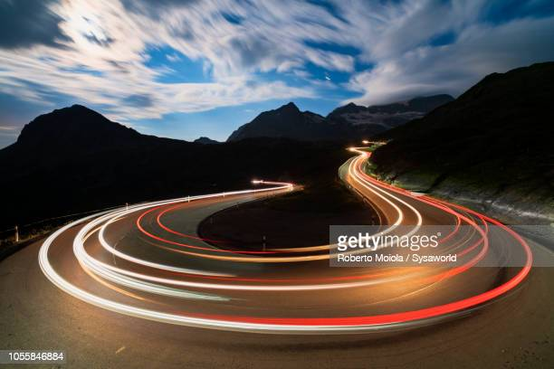 car lights, bernina pass, switzerland - hairpin stock pictures, royalty-free photos & images