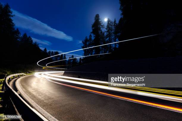 car lights in a full moon night. - mountain pass stock pictures, royalty-free photos & images