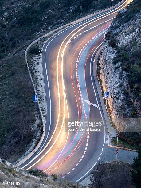 Car lights moving down a curving road at night