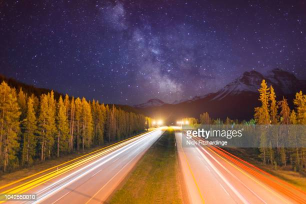 Car lights streaking along the Trans Canada Highway in Lake Louise with the milky way beyond, Lake Louise, Banff National Park, Alberta, Canada