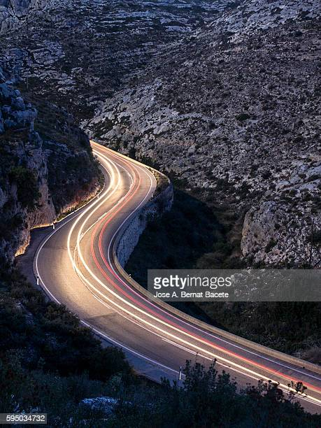 Car lights trails on a road of a mountain gorge