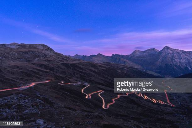 car lights trails on splugen pass road, switzerland - dramatic landscape stock pictures, royalty-free photos & images