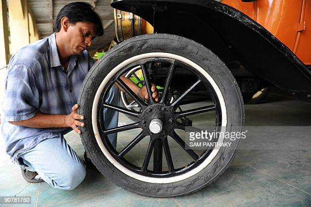 Car Maintenance Supervisor Sunil Shukla inspects one of the four wooden wheels of a US Ford T car from 1910 at 'Auto World' car museum in Kathwada...