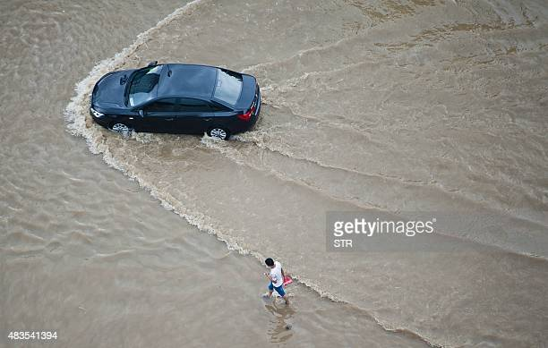 A car makes its way through a flooded street in Wenling in eastern China's Zhejiang province on August 10 2015 after strong storms hit the area...