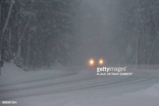 A car makes its way through a snowy road near Elbingerode in the Harz region central Germany on January 18 as many parts of the country are hit by...