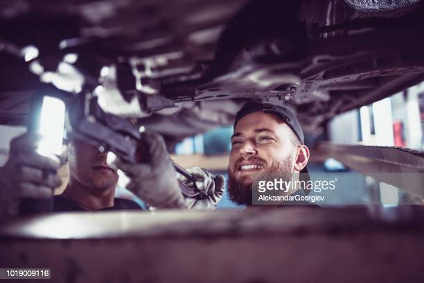 car mechanic and apprentice working on a broken car - chassis stock pictures, royalty-free photos & images