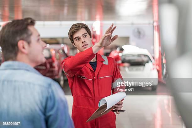 Car mechanic and customer in repair garage