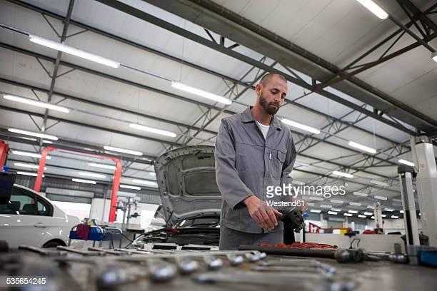 Car mechanic at work in repair garage