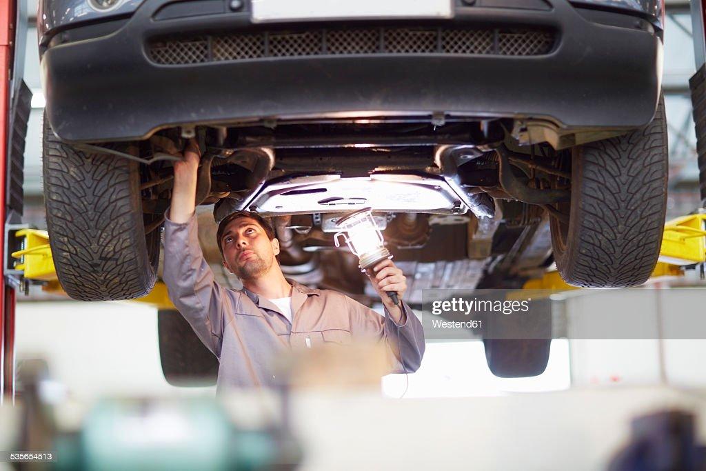Car mechanic at work in repair garage : Stock Photo