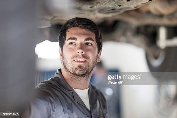 Car mechanic at work in repair garage