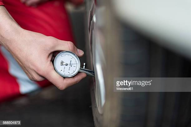 Car mechanic at work in repair garage, tyre pressure gauge