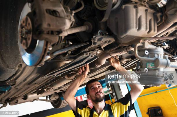 car mechanic at work repairing car chassis - chassis stock pictures, royalty-free photos & images