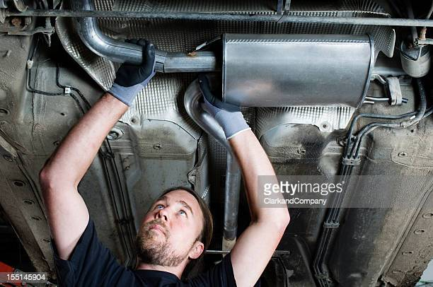 Car Mechanic At Work Replacing an Exhaust