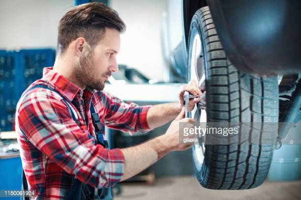 car mechanic changing tires. - flat tire stock pictures, royalty-free photos & images