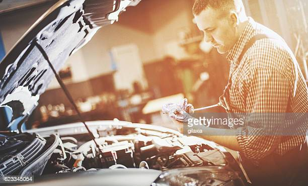 Car mechanic checking engine oil level.