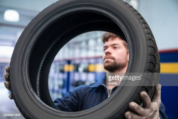 car mechanic checking tire - izusek stock pictures, royalty-free photos & images
