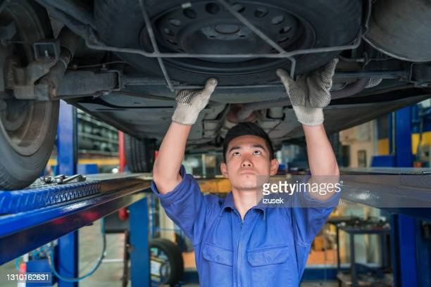 car mechanic checking vehicle chassis - izusek stock pictures, royalty-free photos & images