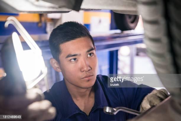 roda de verificação de mecânico de carros na garagem - izusek - fotografias e filmes do acervo