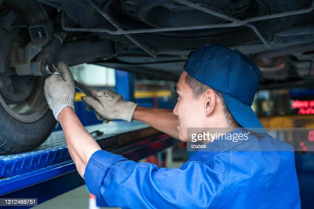 car mechanic checking wheel in garage - one young man only stock pictures, royalty-free photos & images