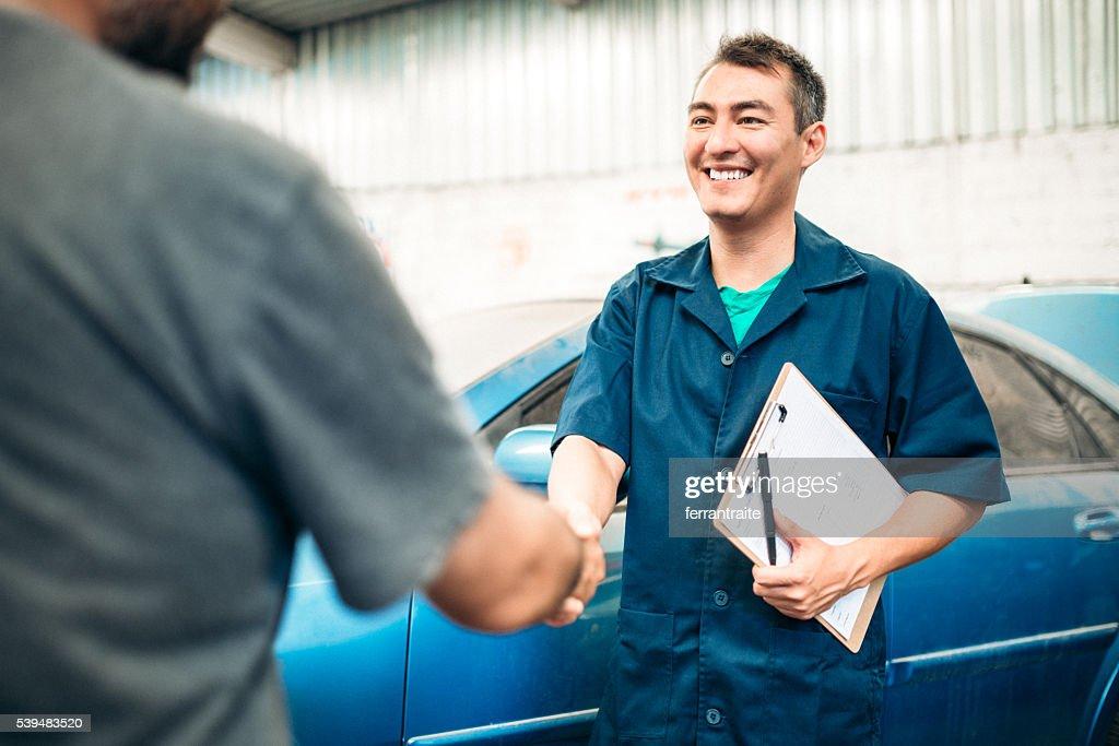 Car mechanic handshakes customer : Stock Photo