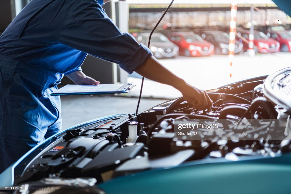 Car mechanic holding clipboard and checking to maintenance vehicle by customer claim order in auto repair shop garage. Engine repair service. People occupation and business job. Automobile technician : Stock Photo
