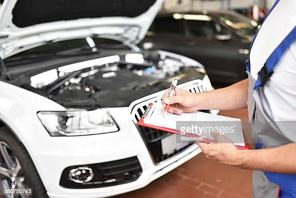car mechanic holding clipboard in a garage - kontrolle stock-fotos und bilder