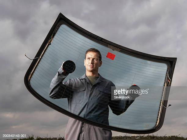 Car mechanic holding rear windscreen with suction pads