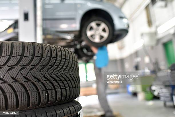 Car mechanic in a workshop, car tires in the foreground
