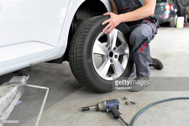 Car mechanic in a workshop changing car tyre