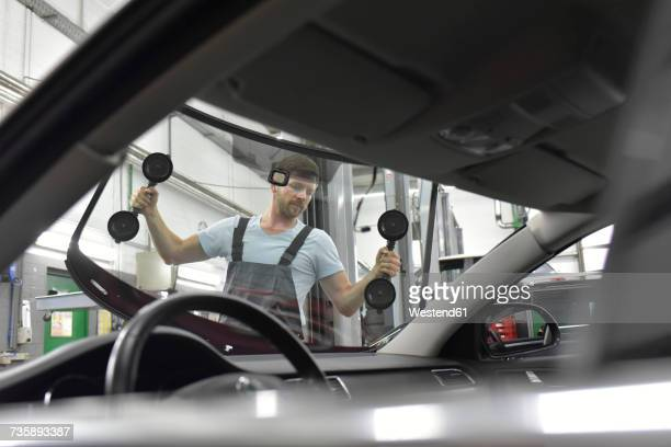 car mechanic in a workshop changing car window - crash photos stock-fotos und bilder