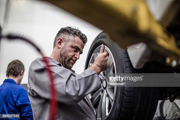 Car mechanic in a workshop changing tire