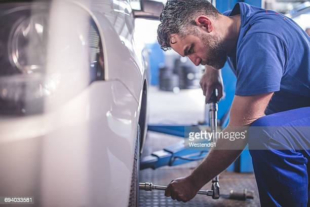 Car mechanic in a workshop changing tyre
