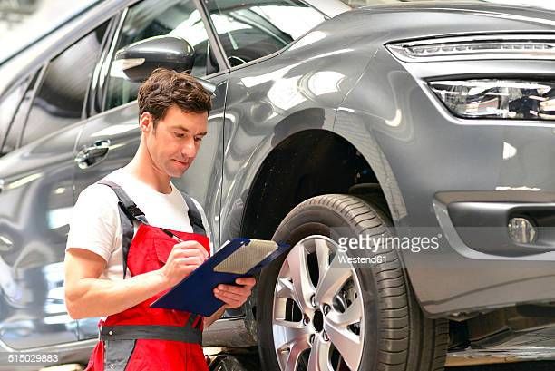 Car mechanic in a workshop holding clipboard