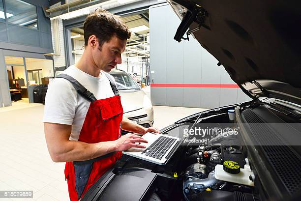 car mechanic in a workshop using modern diagnostic equipment - mechatronics stock pictures, royalty-free photos & images