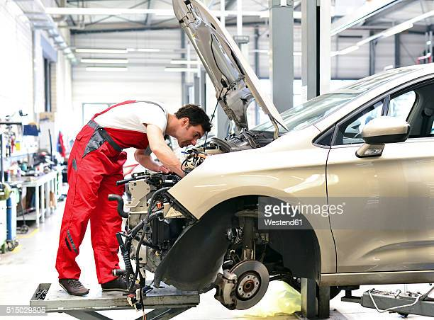 Car mechanic in a workshop working at car